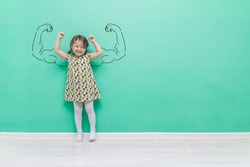 Girl power. The child with hand-drawn muscles in his arms.Funny little girl on a turquoise background with a place for text.