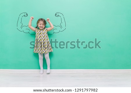 Girl power. The child with hand-drawn muscles in his arms.Funny little girl on a turquoise background with a place for text. #1291797982