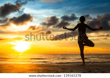 Girl practicing yoga by the sea at sunset.