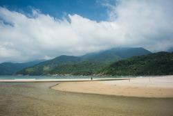 Girl practicing yoga in Martins de Sa beach by the river mouth, near Paraty, south of Rio de Janeiro, Brazil