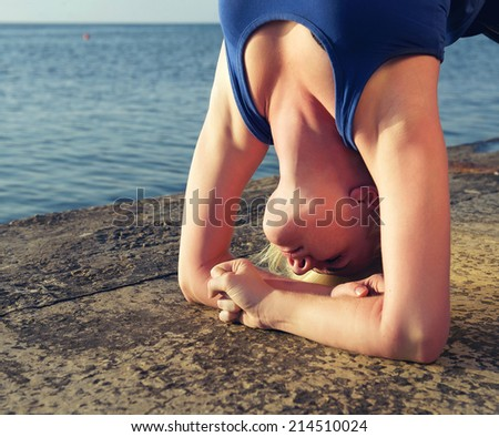 Girl practicing yoga standing on hands. Outdoor. Close-up portrait