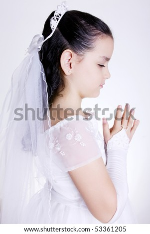 Girl praying with her hands clasped and white dress. First Communion
