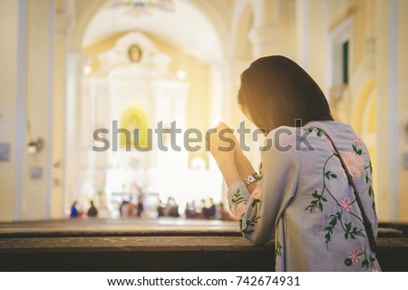 Girl praying worship in a church. Hands folded in prayer, Hope and Religion Concept