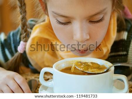 Girl-preschooler eats a tasty meal in cozy restaurant.
