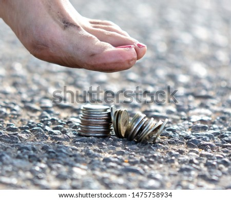Girl presses foot coins on an asphalt road .