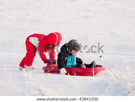 Girl pushing her little brother in a sledge