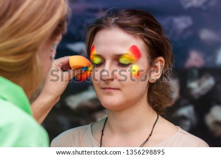 Girl put a picture on her face. Make-up of paints on a body for a carnival. An adult woman is painted for a birthday party. Portrait of a butterfly with colored paints on body.