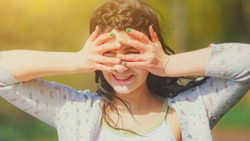 Girl put her hands and fingers to her forehead to shield her eyes from the sun, looks up and happy. Portrait of a beautiful brunette girl covering face by hands of bright sun light, summer vacation.