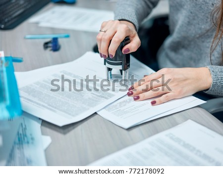 girl puts a stamp on documents in the office