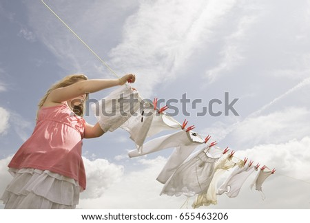 girl putting clothing on a...