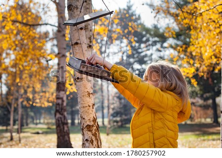 Girl putting food for birds at birdhouse in the forest on warm autumn day. Children taking care of animals outdoor. Outdoor recreation and awesome adventures with kids in fall ストックフォト ©