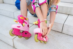 Girl putting her roller skates on the steps in the Park. Kids learning to rollerskating on sunny day. Children playing outside. Active healthy leisure and outdoor sport for kids