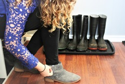 Girl putting on shoes in mudroom