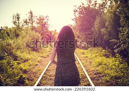 Stock Photo Girl railroad back sunny outside