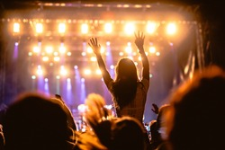 Girl raising her hands and enjoying a great concert.