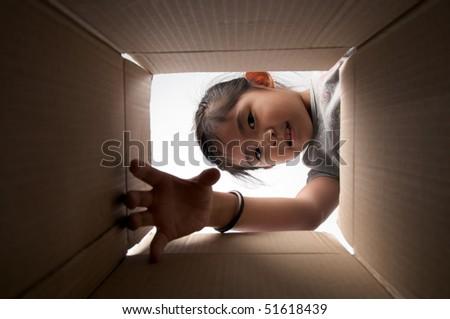 girl reaching for something inside the box