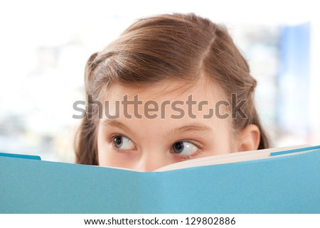 Girl reading a book at school and looking up