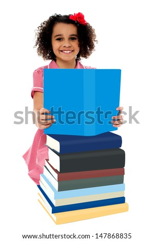Girl reading a book from among pile of books