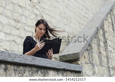 Girl reading a book in a windy day