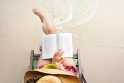 Girl reading a book in sunbed at the beach