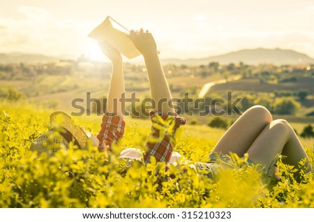 girl reading a book lying on the grass - people, education, nature and lifestyle concept
