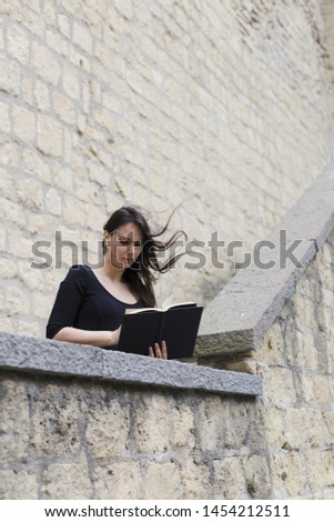 Girl reading a book on a windy day
