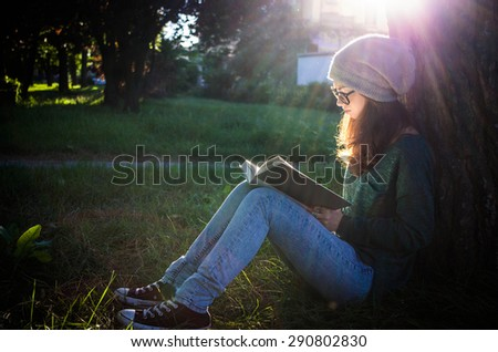 girl reading a book sitting in a park - people, nature and lifestyle concept