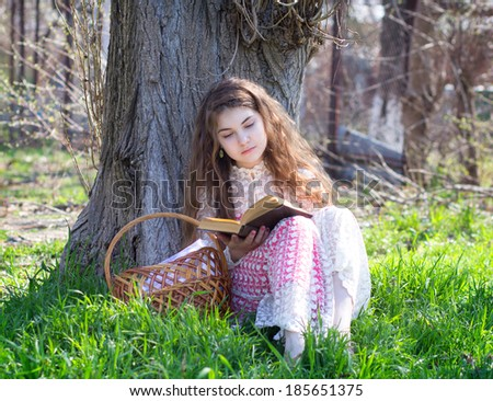 girl reading a book under a tree in nature