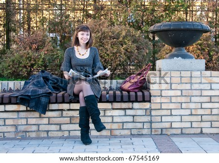 Girl reading a magazine on a park bench