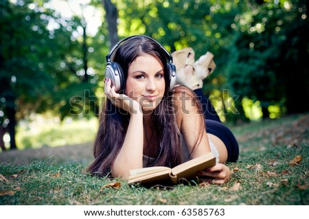Girl reading book and listening music in park