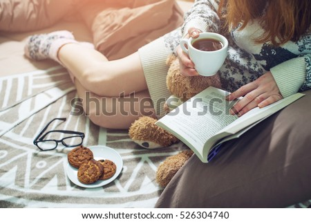 girl reading book in bed with a sweater and warm socks keeping your coffee in hand in the morning. the concept of new year mood. #526304740