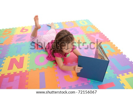 Girl reading book on colorful alphabet floor mat. Isolated on white.