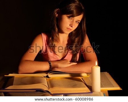 Girl reading book with candle. Black background.