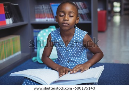 Girl reading braille book while sitting in library