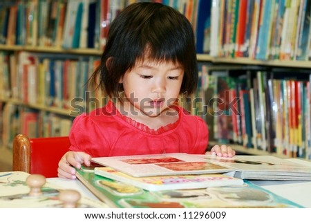 girl reading children's book at library