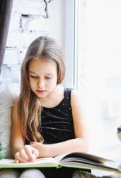 girl reading fairy tales on the window, near the Christmas tree,