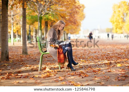 Girl reading in park on a fall day