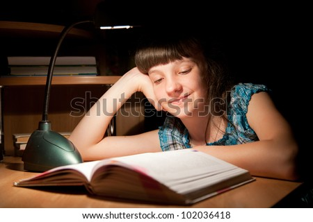 Girl reads a book late at night