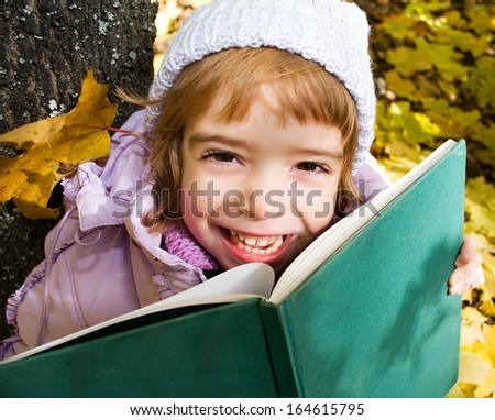 girl reads the book in a  park