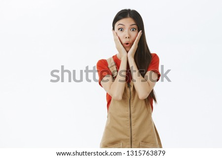 Girl receiving awesome news being surprised and amazed. Emotive young and cute and gentle asian woman gasping from amazement holding palms on cheeks from astonishment posing over white wall