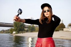 Girl recording vacation with action camera. Swag woman