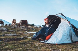 girl relax in campsite, tourist in camp tent on mountain nature, hiker woman enjoys wild horses on valley camping trip