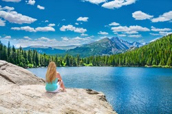 Girl relaxing alone on the rock by lake in beautiful mountains. Woman enjoying nature on hiking trip. Bear Lake. Estes Park. Rocky Mountains National Park, Colorado, USA.