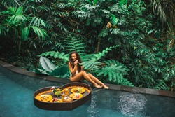 Girl relaxing and eating floating breakfast in jungle pool on luxury villa in Bali. Valentines day or honeymoon surprise. Tropical travel lifestyle. Black rattan tray in heart shape.