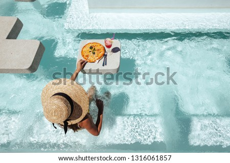 Girl relaxing and eating pizza in the hotel pool. Luxury tropical beach lifestyle.