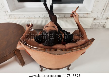 Girl relaxing at home with glass of brandy and cigar
