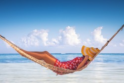 Girl relaxing in a hammock on tropical island beach. Summer vacation in Punta Cana, Dominican Republic.