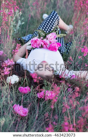 girl relaxing in a meadow with flowers