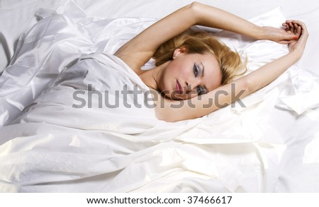 Girl relaxing in bed wrapped in white sheets