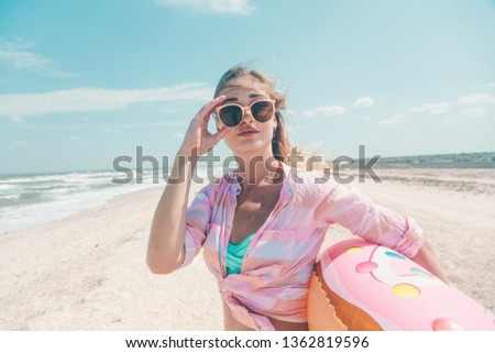 Girl relaxing on donut lilo on the beach. Playing with inflatable ring. Summer holiday idyllic on a tropical island. #1362819596